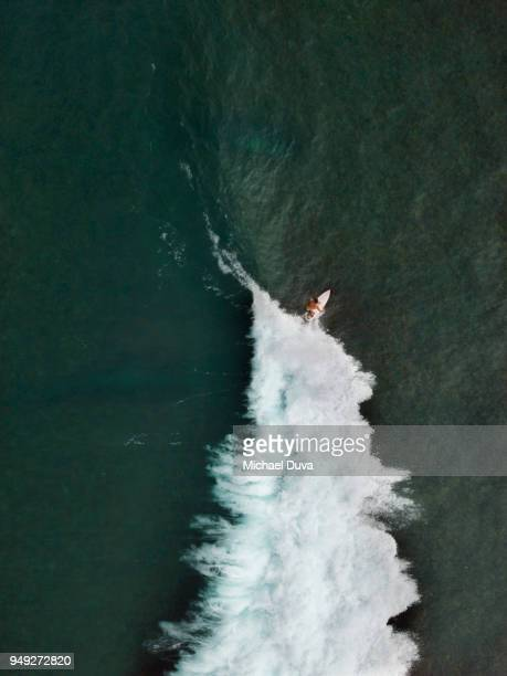 Aerial View of Surfer surfing waves
