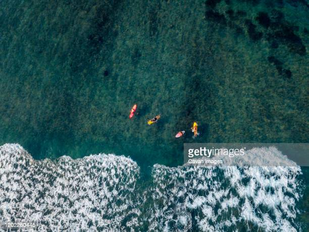 aerial view of surfers in the ocean - denpasar stock pictures, royalty-free photos & images