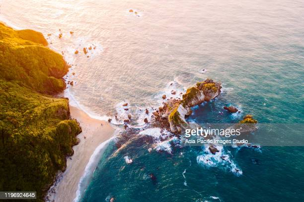 aerial view of surfers on the surfboards at sunset. - north island new zealand stock pictures, royalty-free photos & images