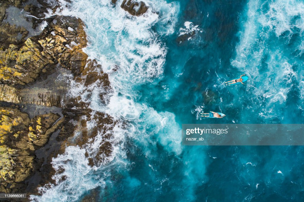 Aerial view of surfers on their surfboards. : Stock Photo