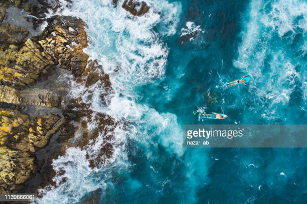 aerial view of surfers on their surfboards. - breaking wave stock pictures, royalty-free photos & images