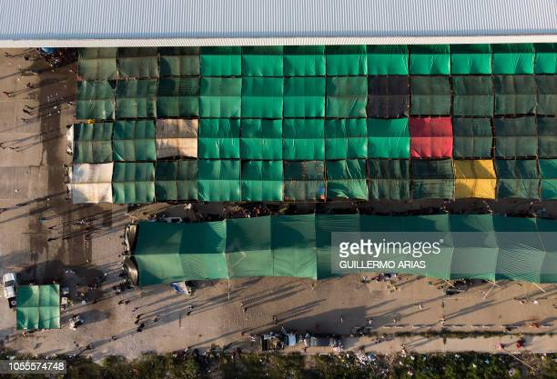 TOPSHOT Aerial view of tents at an abandoned bus station used as temporary shelter for Honduran migrants taking part in a caravan heading to the US...