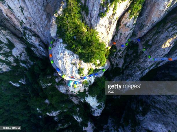 Tents set up by backpackers line up along a plank road on a 2000meterhigh cliff face of the Laojun Mountain during a camping trip on July 21 2018 in...
