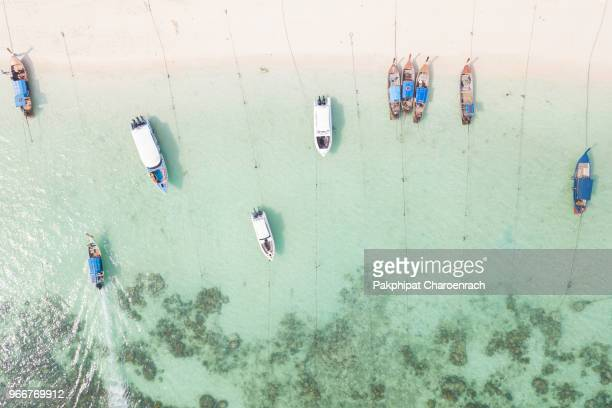 aerial view of thai traditional longtail boats on tropical white sand at sunrise beach, lipe island, thailand. - indian ocean stock pictures, royalty-free photos & images