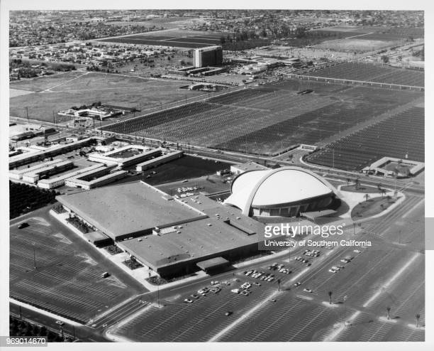 Aerial view of the Anaheim Convention Center, Disneyland parking lots, and a section of the Disneyland monorail, Anaheim, California, early to mid...