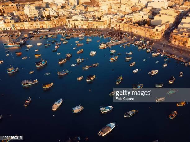 aerial view of the boats at marsaxlokk harbour in malta. a fishing village in the south of malta. - malta fotografías e imágenes de stock