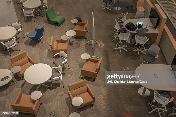 Aerial view of the Brody Learning Commons at Johns Hopkins University atrium with only one student sitting at a table 2016 Courtesy Eric Chen
