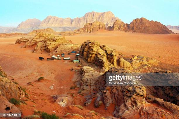 aerial view of the camp for tourist with a bedouin tent, in yellow red after sunrise wadi rum dramatic desert, wilderness of sandstone and granite in canyon jordan - paisajes de jordania fotografías e imágenes de stock