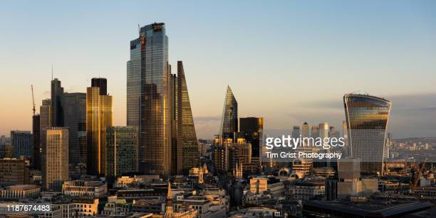 aerial view of the city of london's financial district at dusk and canary wharf in the distance. london, uk. - tim grist stock pictures, royalty-free photos & images