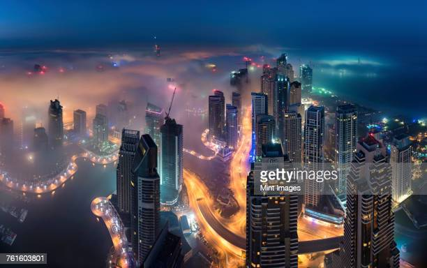 Aerial view of the cityscape of Dubai, United Arab Emirates at dusk, with illuminated skyscrapers and the marina in the foreground.