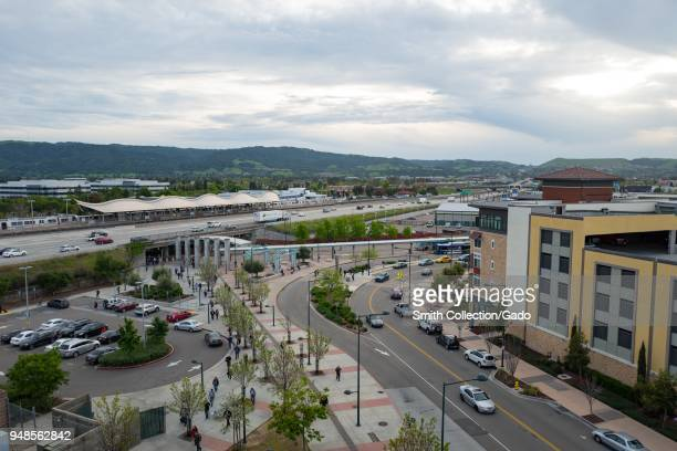 Aerial view of the Dublin Pleasanton Bay Area Rapid Transit commuter rail station in downtown Dublin California with mountains and apartment...