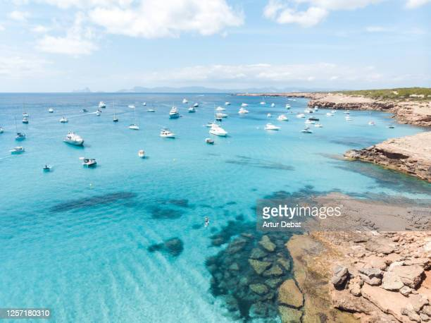 aerial view of the formentera island with paradise beach and yachts in the mediterranean sea with the ibiza island silhouette. toma aérea de la isla de formentera con playas paradisiacas y yates. - vista aérea stock pictures, royalty-free photos & images