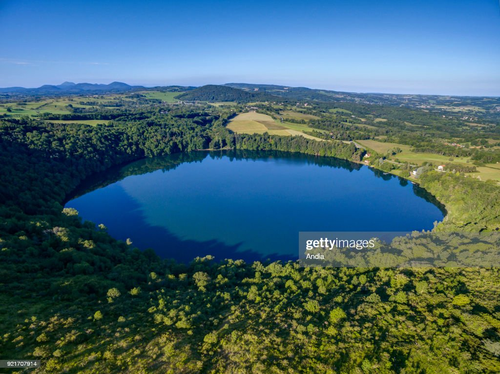 Aerial view of the Gour de Tzenat, a volcanic lake located in the Chaine des Puys mountain range in the Massif Central, Puy-de-Dome department, in Charbonnieres-les-Vieilles (central France). The crater lake and the surrounding mountains viewed from above.