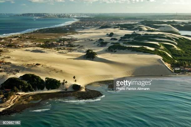 Aerial view of the isthmus of Genipabu covered with sand dunes formation and tropical flora in the district of Extremos, Rio Grande do Norte, Brazil