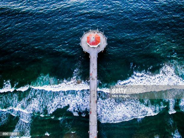 Aerial view of the Manhattan Beach Pier and waves breaking on the shore.