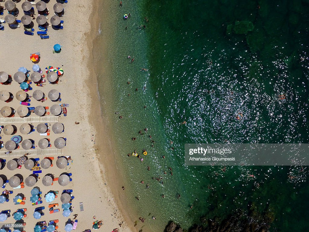 Aerial view of The Mega beach with umbrella and sunbeds on August 06, 2015 in Syvota, Greece. Mega beach is the largest beach of the region .It is organized and its green waters are usually cool. The beach has pebbles and is surrounded by shops so that guests can enjoy a meal and a coffee.
