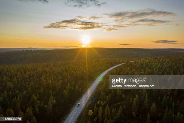 aerial view of the midnight sun shining over a remote road in the finnish lapland, with one solitary car on the road - freie straße stock-fotos und bilder
