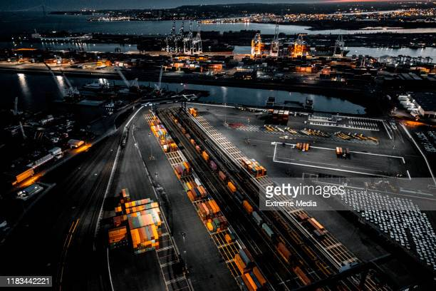 aerial view of the new jersey shipyard with numerous cranes, gantries and shipping containers, captured at golden hour - commercial dock stock pictures, royalty-free photos & images