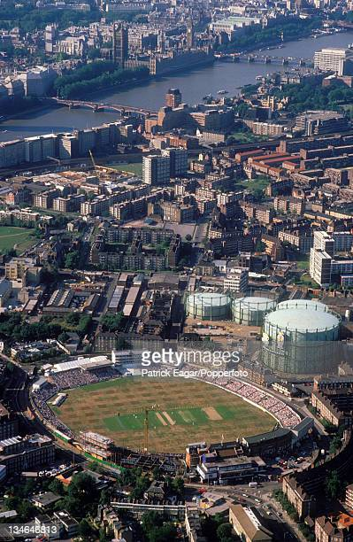Aerial view of the Oval, showing building work on the new pavilion and stands. The Test match is in progress. The Houses of Parliamernt and the River...