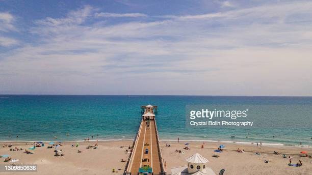 aerial view of the pier in juno beach, florida with bright blue ocean water at mid-day during spring break in march of 2021 - juno beach florida stock pictures, royalty-free photos & images
