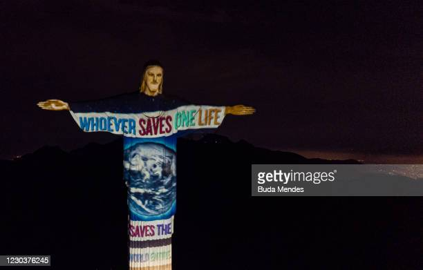 Aerial view of the planet Earth on the illuminated statue of Christ the Redeemer in a honor of the medical workers amidst the Coronavirus pandemic on...