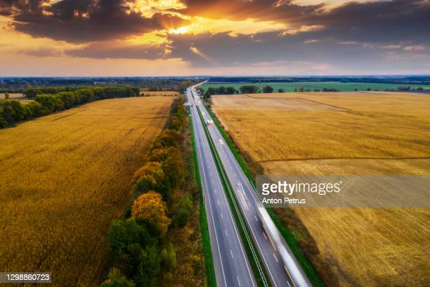 aerial view of the road between green fields at sunset - ukraine stock pictures, royalty-free photos & images