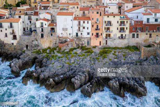 aerial view of the rocky coast and the houses of cefalu from the sea in windy and stormy weather. big waves beat against stones. sicily, italy - abruzzi stock pictures, royalty-free photos & images