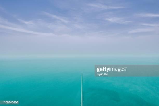 aerial view of the sea divided by road - liyao xie - fotografias e filmes do acervo