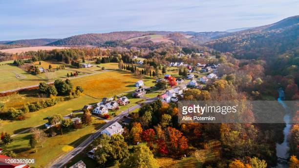 aerial view of the small town surrounded by the forest in the mountain in autumn morning. - pennsylvania stock pictures, royalty-free photos & images