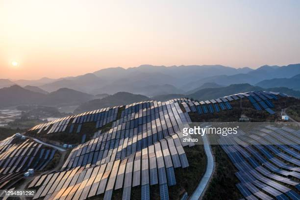 aerial view of the solar power plant on the top of the mountain at sunset - factory stock pictures, royalty-free photos & images