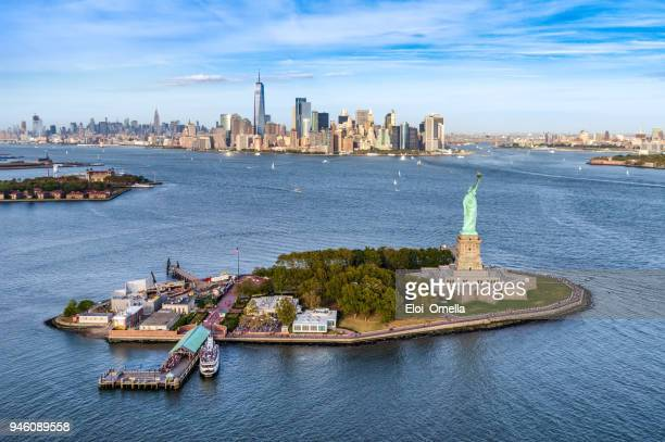 aerial view of the statue liberty island in front of manhattan skyline. new york. usa - ellis island stock photos and pictures