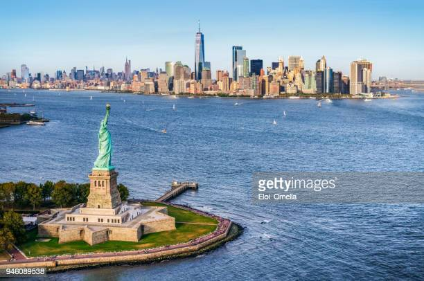 aerial view of the statue of liberty in front of manhattan skyline. new york. usa - helicopter photos stock pictures, royalty-free photos & images