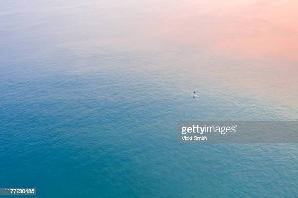 aerial view of the sunrise colors reflecting on the blue ocean with a single surfer - sea stock pictures, royalty-free photos & images