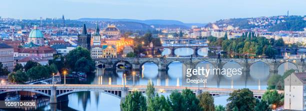aerial view of the the charles bridge and vltava river in prague at twilight, czech republic - international landmark stock pictures, royalty-free photos & images