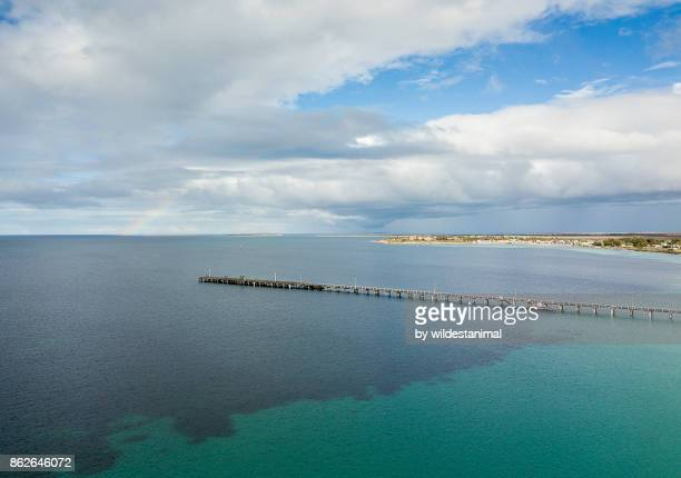 Aerial view of the Tumby Bay Jetty on a sunny day with a rainbow in the sky.