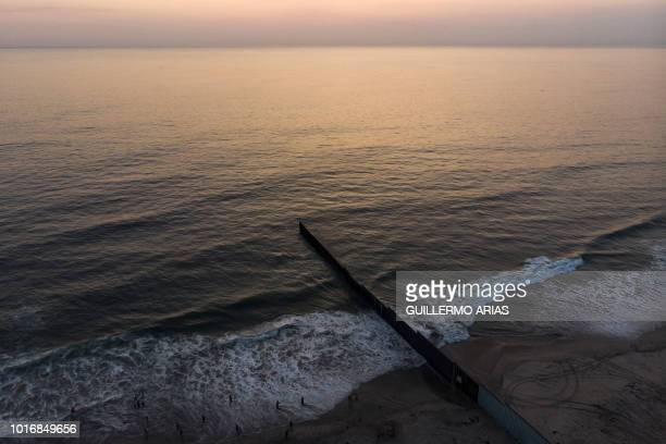 Aerial view of the United States Mexico border fence extending into the Pacific ocean at Playas de Tijuana Baja California state Mexico on August 10...