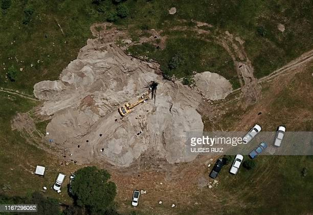 TOPSHOT Aerial view of the zone where forensic experts are working using an excavator to dig in an old 30meter well turned into a mass grave where up...