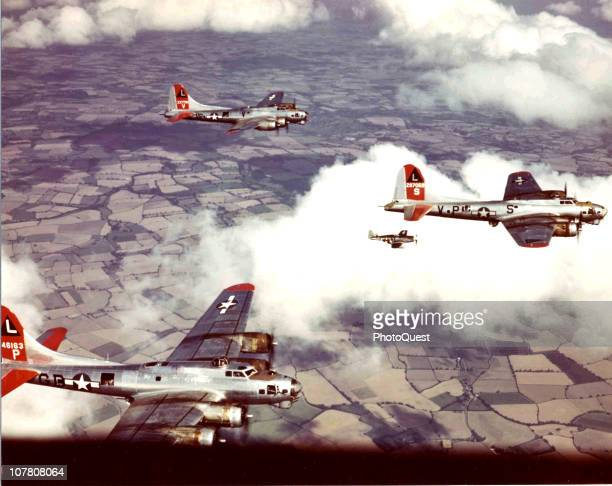 Aerial view of three Boeing B17 Flying Fortress bombers escorted by a North American P51 Mustang fighter as they practice formations over England...