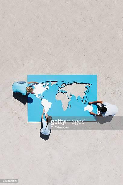 Luftbild von drei Leute Welt Karte puzzle im Freien