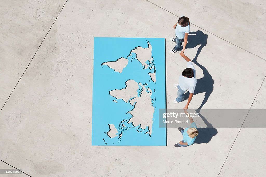 Aerial view of three people holding hands with looking down at world aerial view of three people holding hands with looking down at world map stock photo gumiabroncs Gallery