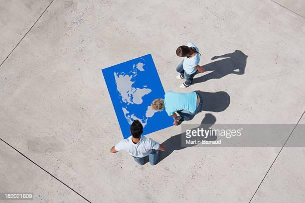 Luftbild von drei Personen, die am Welt Karte puzzle