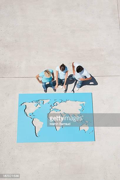 Luftbild von drei Personen, Blick nach unten auf der Weltkarte