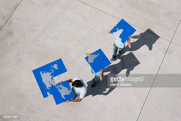 Luftbild von drei Personen mit Stücken der Weltkarte