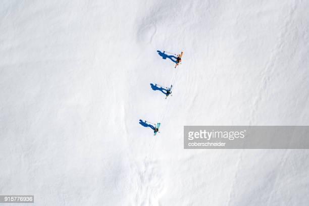 Aerial view of three skiers and their shadows in the Alps, Sportgastein, Salzburg, Austria
