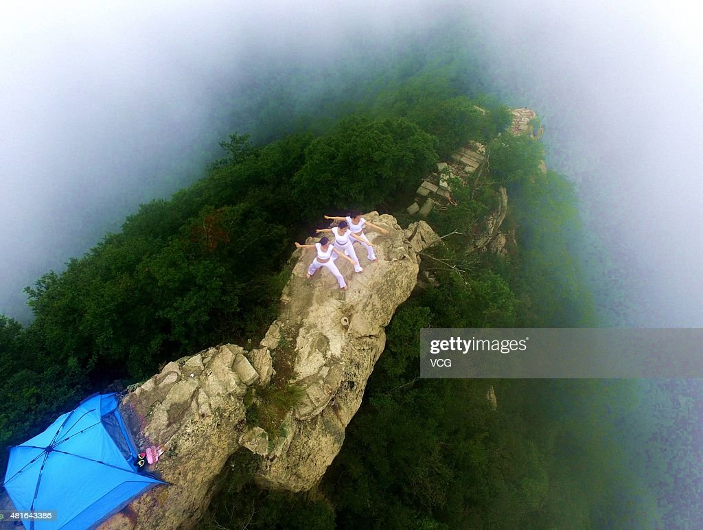 Aerial view of three women doing yoga on a 2,000-meter high precipice on Laojun Mountain, main peak of Funiu Mountain, during Laojun Mountain Camping Festival on July 18, 2015 in Luoyang, Henan Province of China.