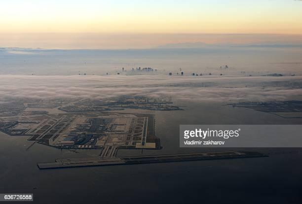 aerial view of tokyo in fog and haneda airport - haneda tokyo stock photos and pictures
