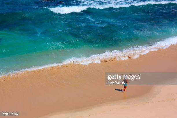 Aerial view of tourist walking on tropical beach