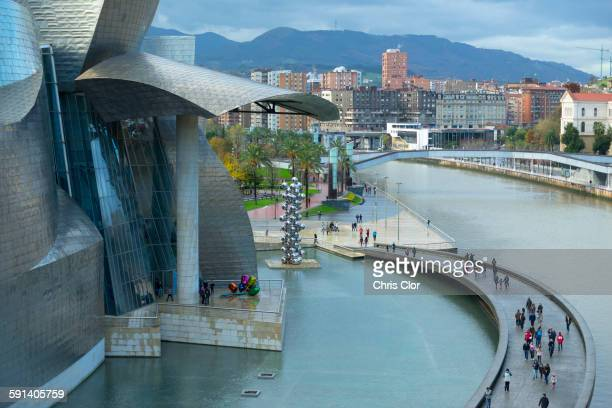 aerial view of tourists on walkway over urban canal, bilbao, biscay, spain - bilbao stockfoto's en -beelden