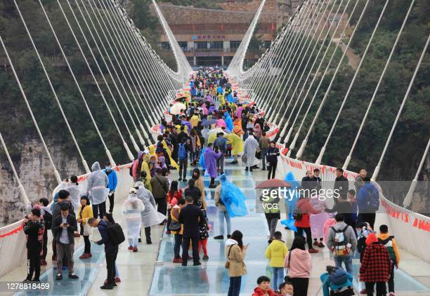 Aerial view of tourists visiting a 430-meter-long and 6-meter-wide glass bridge hanging between two steep cliffs 300 meters above the ground during...