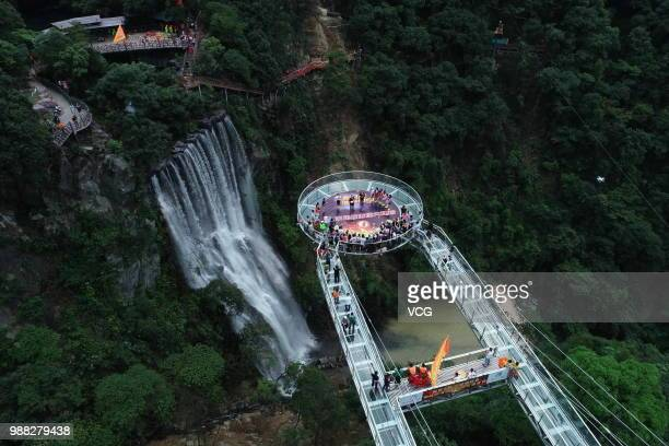Aerial view of tourists visiting a glass bridge featuring a circular observation deck along a cliff at the Gulongxia scenic spot on June 28 2018 in...